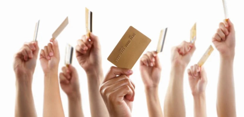 Many credit cards in hands shutterstock_55566304