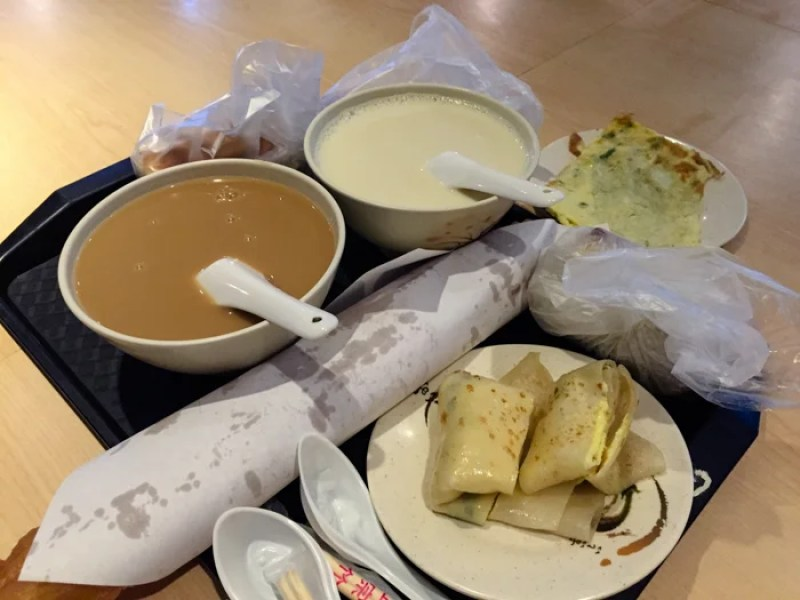 A traditional Taiwanese breakfast often includes rice and soy milk (in bowls), dan bing (bottom right), and fried crullers (center, in paper).