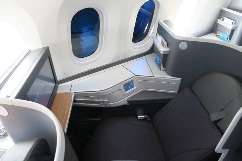 A partially-reclined seat with a mostly-dimmed window.