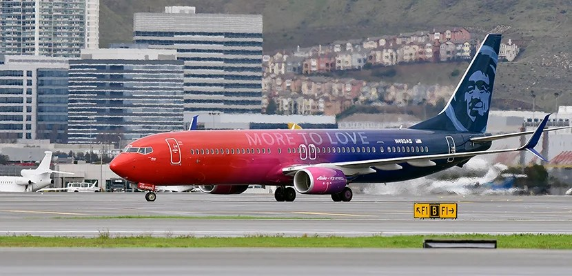 """In this photo released by Alaska Airlines, A specially painted, co-branded Alaska Airlines and Virgin America 737-900ER aircraft, painted in shimmering red, purple and blue and featuring the slogan """"More to love,"""" lands at San Francisco International Airport on December 14, 2016 in San Francisco, CA. The newly painted aircraft is part of the merger celebration of Alaska Airlines and Virgin America. (Photo by Alaska Airlines, Bob Riha, Jr.)"""