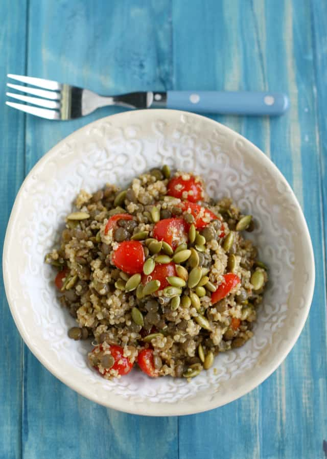 A tasty and healthy salad made with lentils, quinoa, tomatoes, and pepitas.