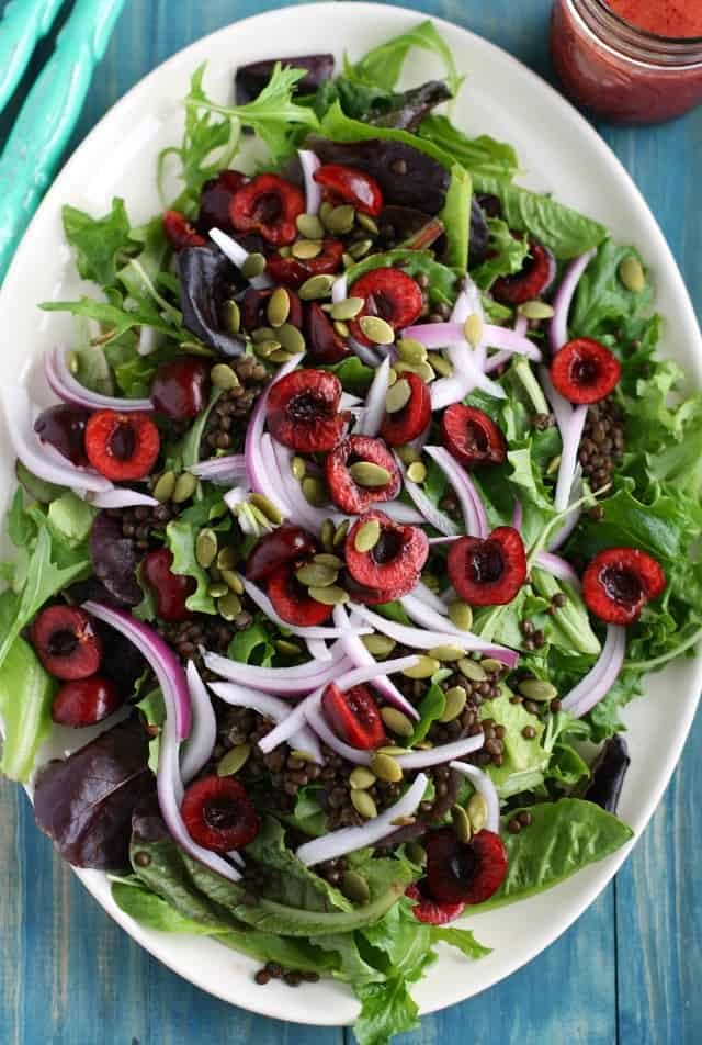 A fresh summer green salad with black lentils and fresh cherries. This healthy and antioxidant salad is topped with a chery vinaigrette. #antioxidants