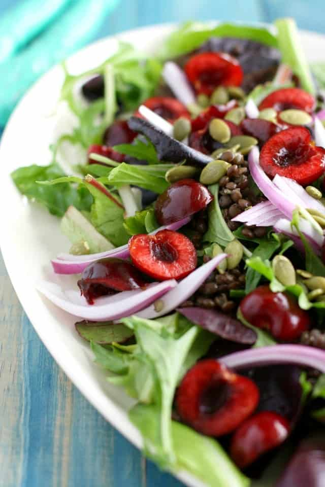 Simple and summery green salad with black lentils and fresh cherries. A sweet and tart vinaigrette finishes this healthy salad! #antioxidants #vegan
