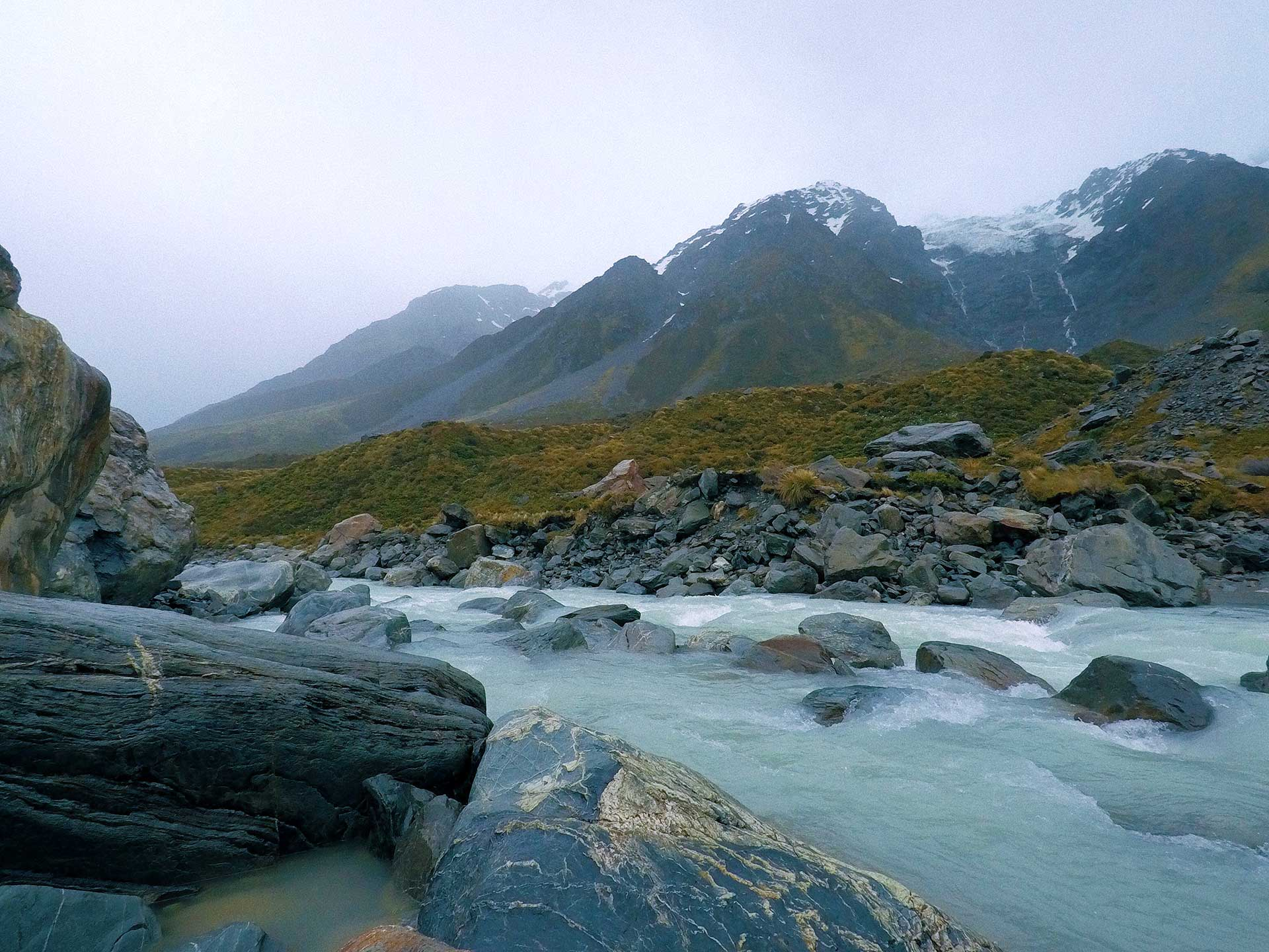 thereafterish, new zealand bright blue cold glacial Hooker River rushing through mountainous valley