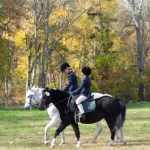 Vicki (on Devil) and Mia (on Chrissy) walking their ponies while waiting to jump