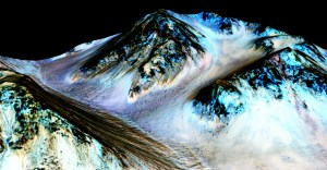 These dark, narrow, 100 meter-long streaks called recurring slope lineae flowing downhill on Mars are inferred to have been formed by contemporary flowing water. Recently, planetary scientists detected hydrated salts on these slopes at Hale crater, corroborating their original hypothesis that the streaks are indeed formed by liquid water. The blue color seen upslope of the dark streaks are thought not to be related to their formation, but instead are from the presence of the mineral pyroxene. The image is produced by draping an orthorectified (Infrared-Red-Blue/Green(IRB)) false color image (ESP_030570_1440) on a Digital Terrain Model (DTM) of the same site produced by High Resolution Imaging Science Experiment (University of Arizona). Vertical exaggeration is 1.5. Credits: NASA/JPL/University of Arizona