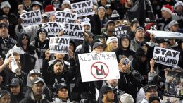 Raiders fans hold signs asking the team not to move to Los Angeles. Photo: Kirby Lee, FoxSports.com