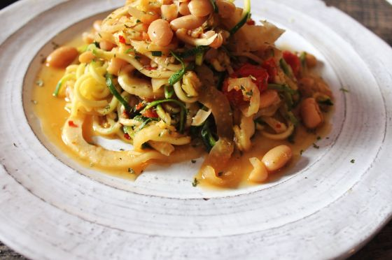 closeup shot of zucchini noodles with braised fennel, tomato and beans!