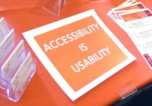"A poster with the words, ""accessibility is usability"" laying on the WeCo display table."