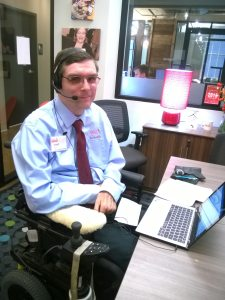 Man seated in a wheel chair wearing a headset and preparing to show speech recognition software.