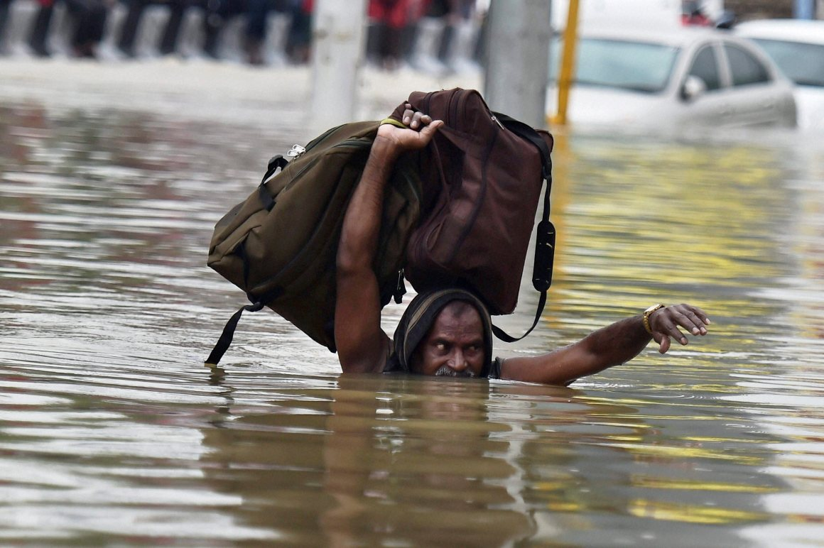 A man moves to a safe place from flooded Kotturpuram during heavy rains in Chennai on Wednesday. Credit: PTI