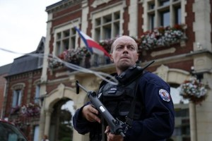 A policeman secures a position in front of the city hall after two assailants had taken five people hostage in the church at Saint-Etienne-du -Rouvray near Rouen in Normandy, France, July 26, 2016. Credits: REUTERS/Pascal Rossignol