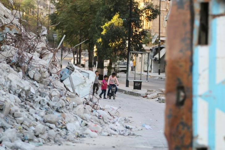 Children play with a bicycle near the rubble of damaged buildings in the rebel-held Bab al-Hadid neighbourhood of Aleppo, Syria, September 14, 2016. Credit: REUTERS/Abdalrhman Ismail