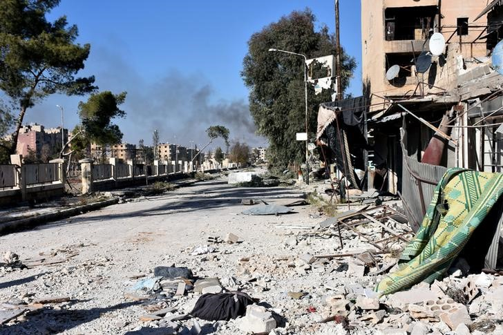 Smoke rises behind a damaged street in Hanano housing district after government forces took control of the area in Aleppo, Syria in this handout picture provided by SANA on November 27, 2016. SANA/Handout via REUTERS