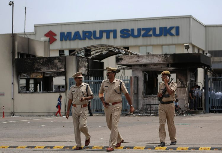 Police officials walk outside the Maruti Suzuki's plant in Manesar, located in the northern Indian state of Haryana, July 19, 2012. Police were searching on Thursday for 3,000 people they want to detain after one person was killed and scores injured in a riot at the Maruti Suzuki factory in Manesar. Hundreds of police have secured the plant, arresting 88 people after property was smashed and parts of the factory set on fire during Wednesday's violence, police said. REUTERS/Ahmad Masood (INDIA - Tags: BUSINESS CIVIL UNREST MILITARY TRANSPORT)