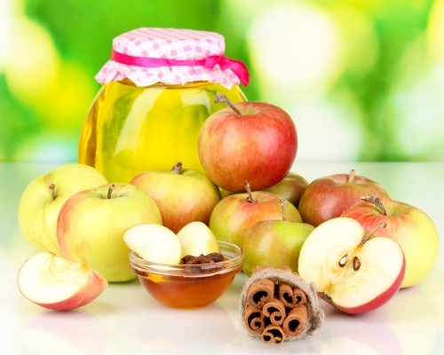 Honey and apples with cinnamon on natural background