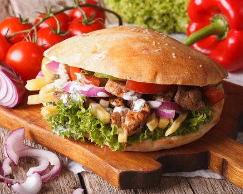 Doner kebab with meat, vegetables and french fries closeup. horizontal