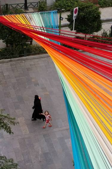 Whispering Rainbow by Hanieh Alizadeh, Mahmoud Ganji, Mehdi Rabie (EOT design studio). Satin ribbon. Hefdah-E-Shahrivar Street, Tehran, 2015. Photo via EOT design studio's Facebook.