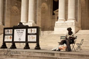 homeless_man_sits_and_looks_through_bags_outside_new_york_public_library_with_find_the_future_sign