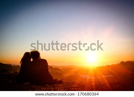 Couple in love enjoying tender moments during sunset at Twin Peaks in San Francisco - Emotional concept of relationship with travel boyfriend and girlfriends relaxing together  - stock photo