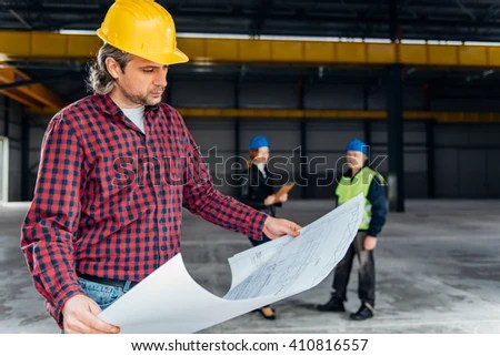 Construction Worker Safety Helmet Reading Blueprints Stock Photo - reading blueprints