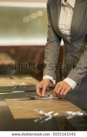 Female Catering Manager Putting Forks Knives Stock Photo (Royalty