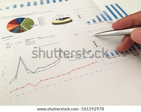 Pen Point On Business Report Charts Stock Photo (Royalty Free