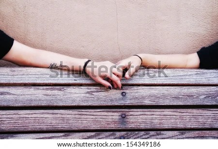 two people holding hands on a bench - stock photo