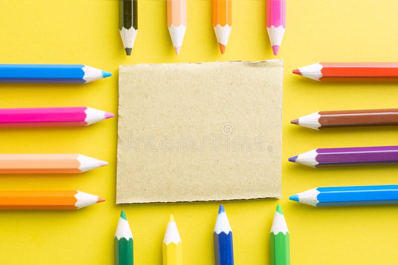 Colored Pencils And Notepad Recycle On Yellow Paper Background - colored writing paper