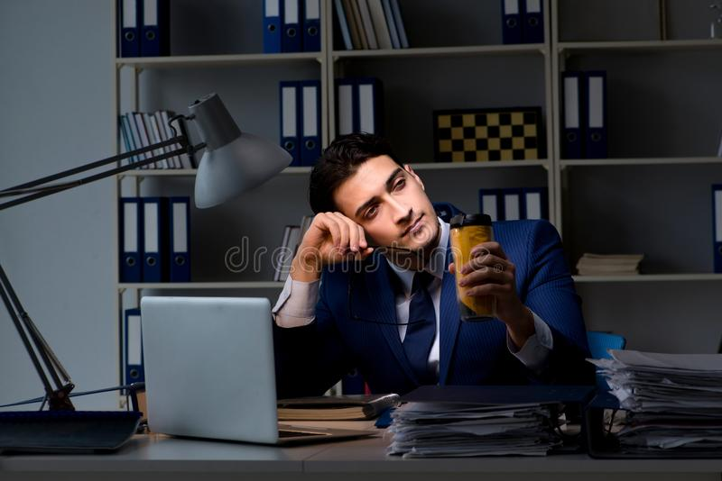 The Employee Working Late And Drinking Strong Coffee To Stay Awake