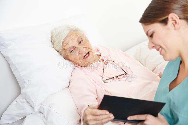 Geriatric Nurse Reading Book Stock Image - Image of aloud