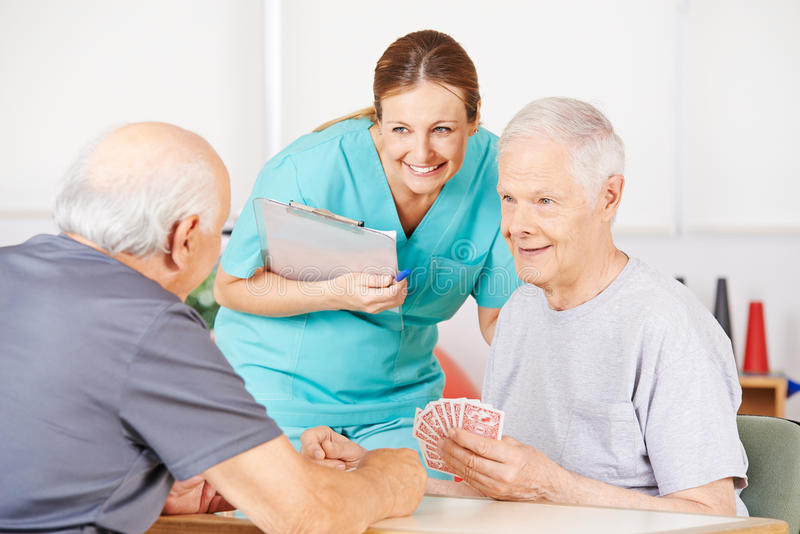 Geriatric Nurse Watching Old Men Playying Cards Stock Image - Image