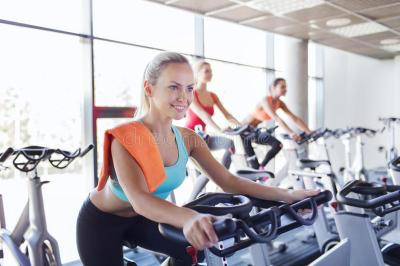 Group Of Women Riding On Exercise Bike In Gym Stock Photo ...