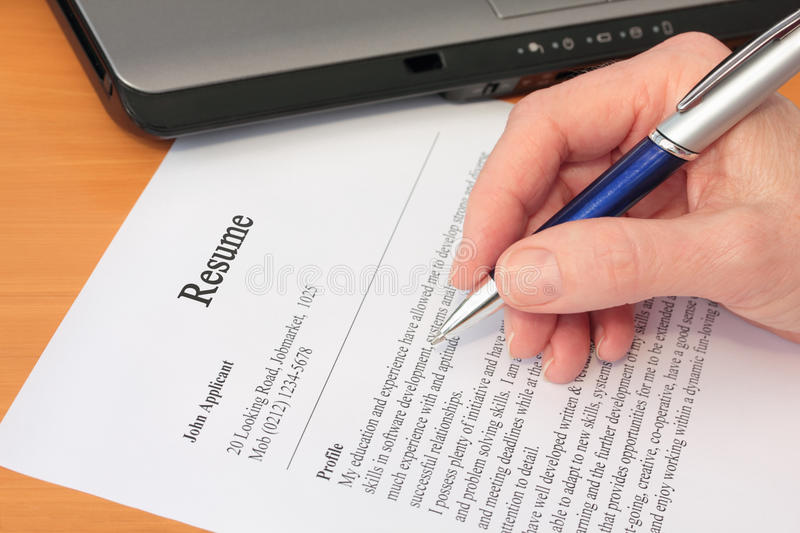 Hand With Pen Proofreading A Resume By Laptop Stock Image - Image of - resume proofreading
