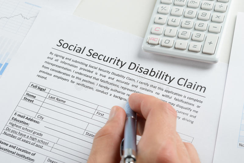 Person Hand With Pen Filling Social Security Disability Form Stock