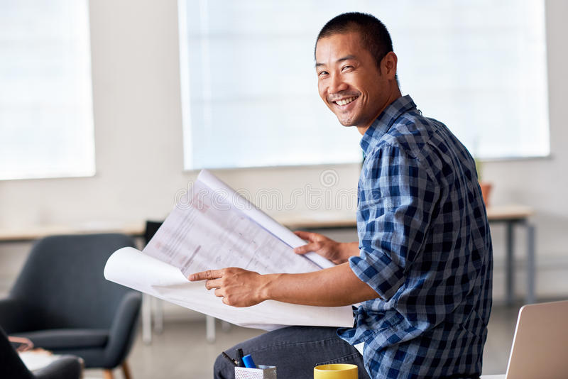 Smiling Asian Architect Reading Blueprints In An Office Stock Image - reading blueprints