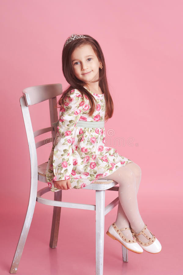 Smiling Girl Sitting On Chair In Room Stock Photo Image