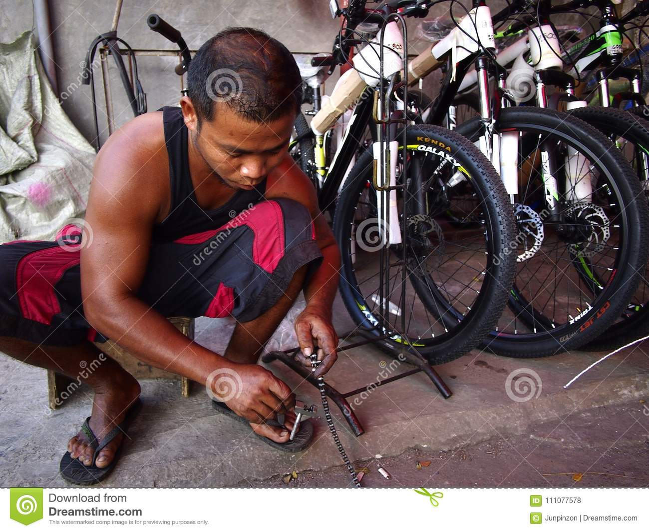 A Bike Store A Bike Repair Man Fixes A Bicycle Chain At A Bike Store Editorial