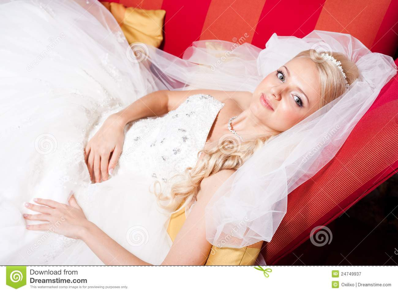 Beautiful bride wearing white wedding dress and veil lying on red sofa