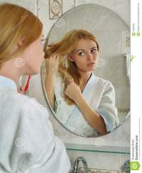 The Beautiful Girl Looks In A Mirror In A Bathroom Stock ...