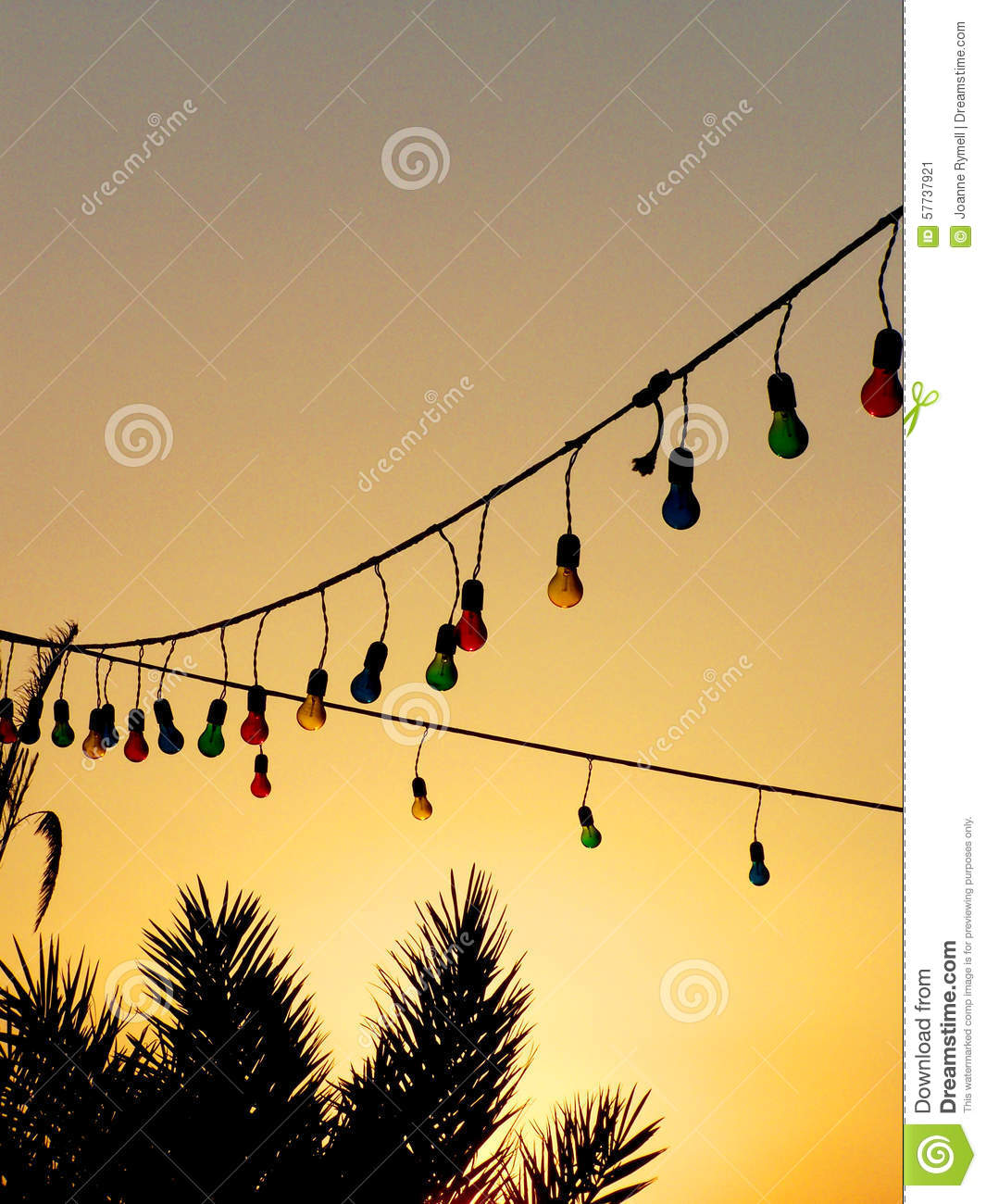 Beach Hanging Lights Colourful Light Bulbs And Palm Trees At Sunset Stock Photo