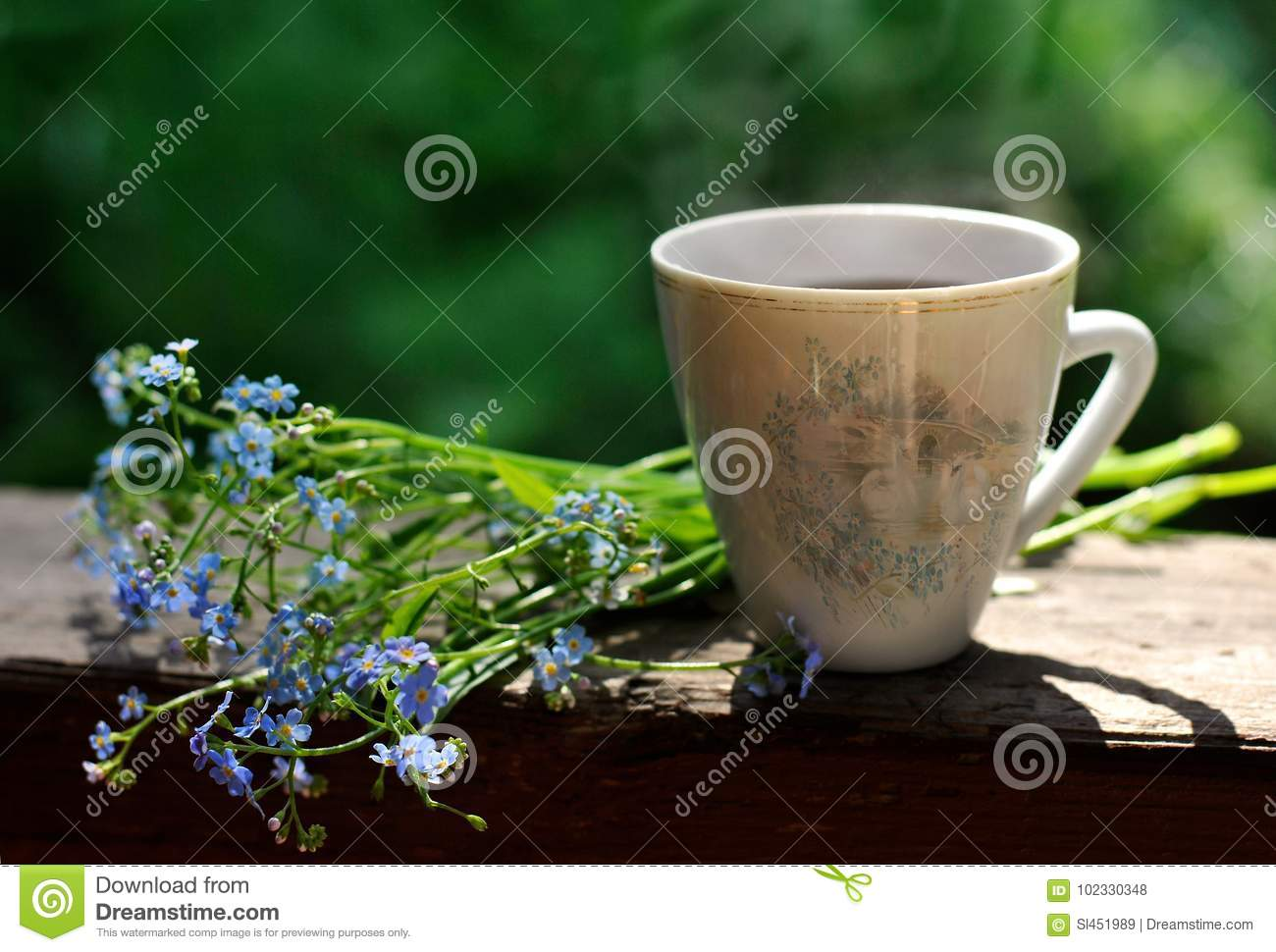 Bru Coffee Green Garden A Cup Of Coffee And Blue Flowers Near It On A Green Garden