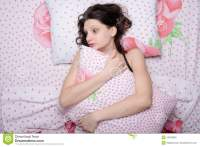 Frightened Young Girl Hugging A Pillow While Lying In Bed ...