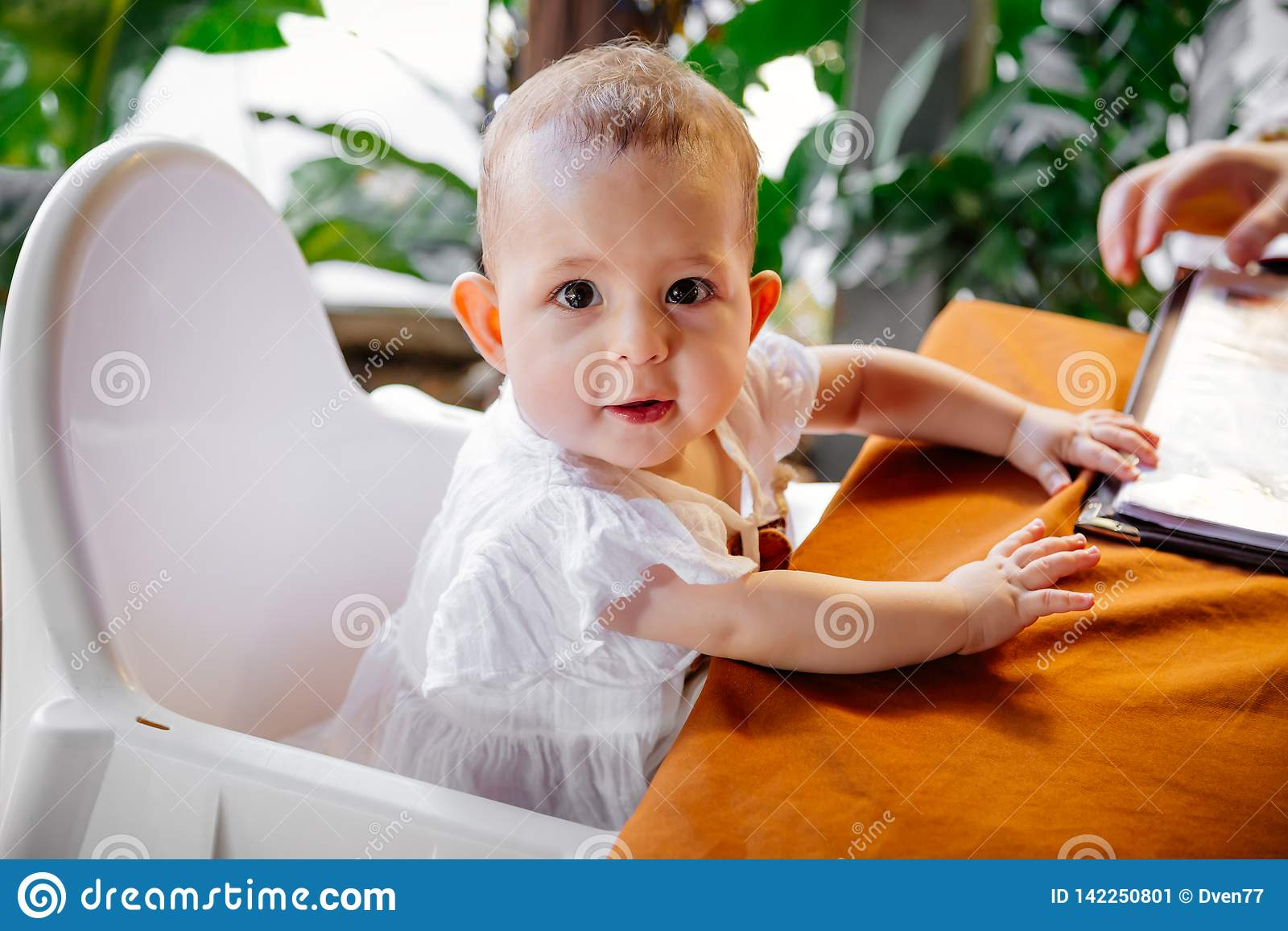 Infant Learning Chair Infant Girl Is Sitting On A Baby High Chair In A Street Cafe