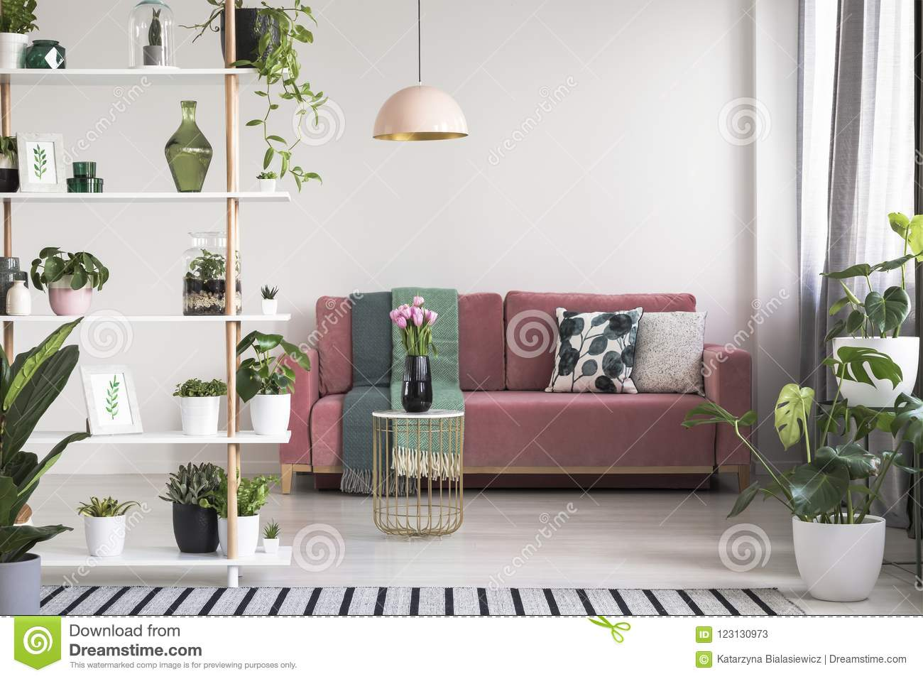 Interio Sofa Marilyn Lamp Above Table With Flowers In Front Of Red Sofa In White Living