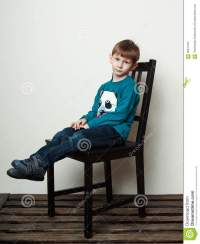Little Sad Boy Is Sitting On The Chair Along Stock Image ...