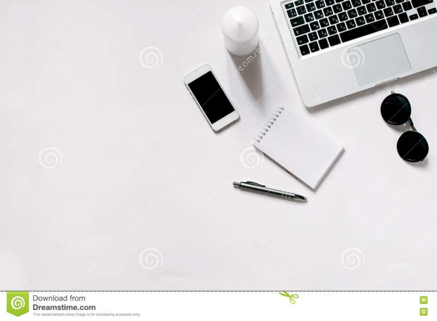 Minimalistic workplace with laptop in flat lay style. White background.