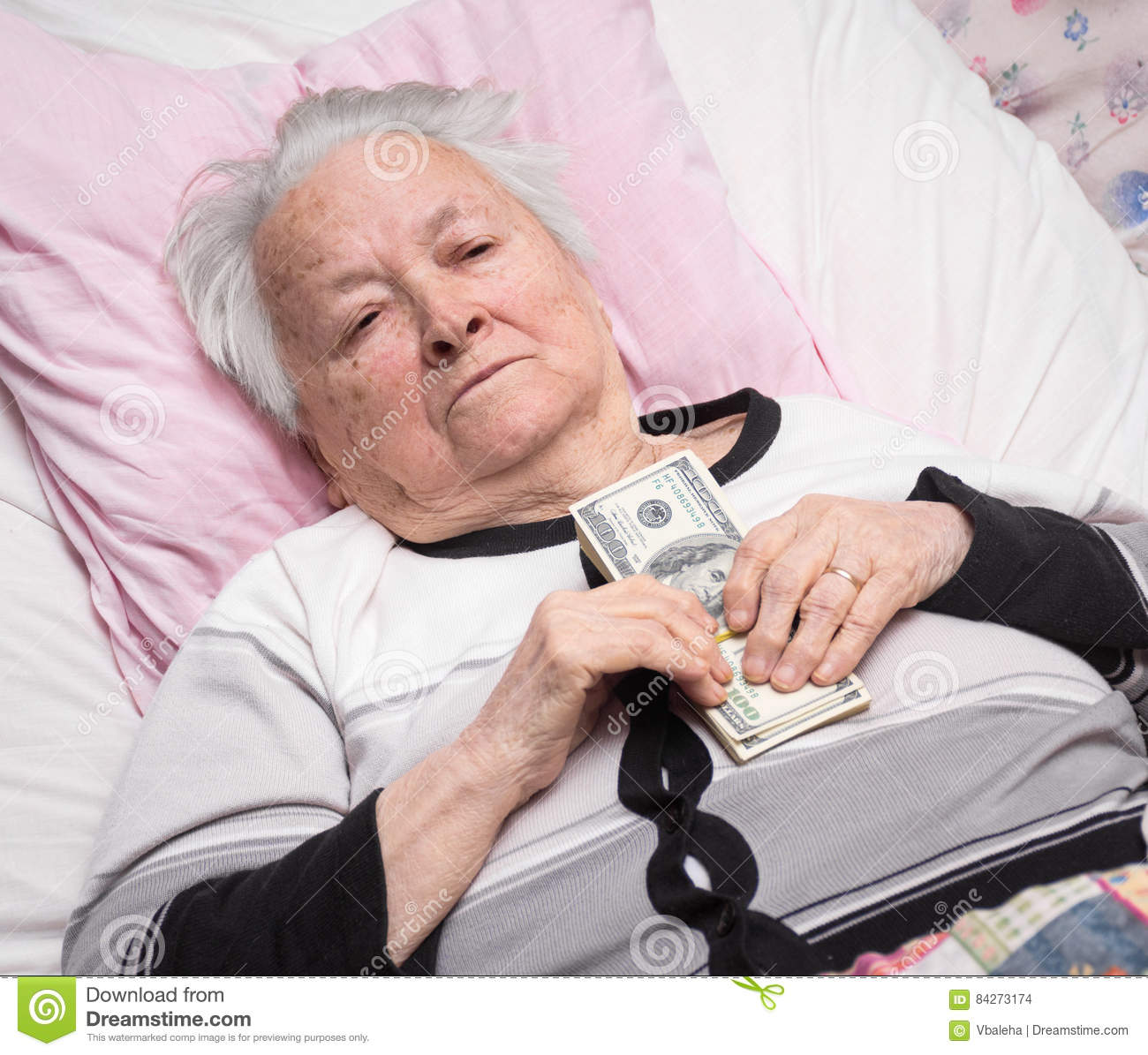 How To Be More Confident In Bed Old Woman Lying In Bed And Holding Dollar Cash Stock Photo