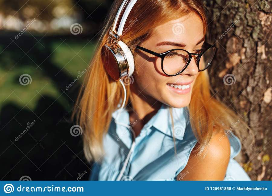 Portrait of a beautiful positive student girl listening to music with headphones, outdoors, wearing glasses