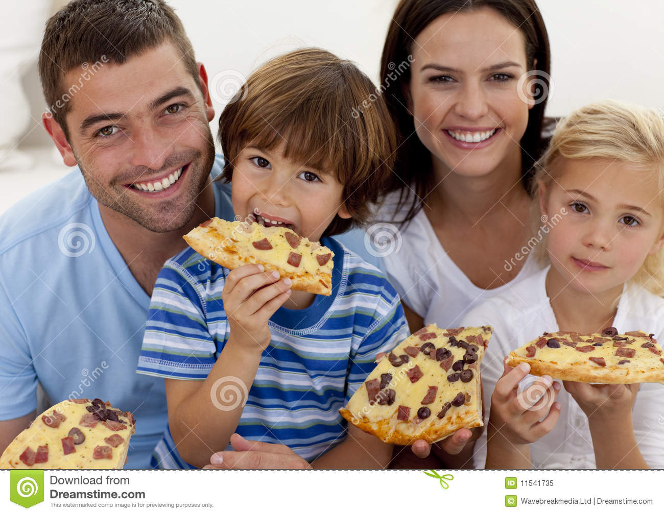 Portrait Of Family Eating Pizza In Living